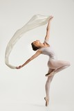 Young ballerina dancing with piece of silk fabric