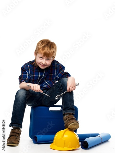 Funny little mechanic boy with wrench tools sitting on toolbox