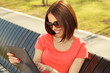 Young woman sits in a park on a wooden bench and using tablet PC