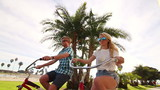Young Happy Couple Riding Bikes At Beach Slow Motion
