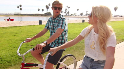 Young Happy Couple Riding Bikes At Beach Park