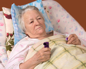Sick old woman lying at bed