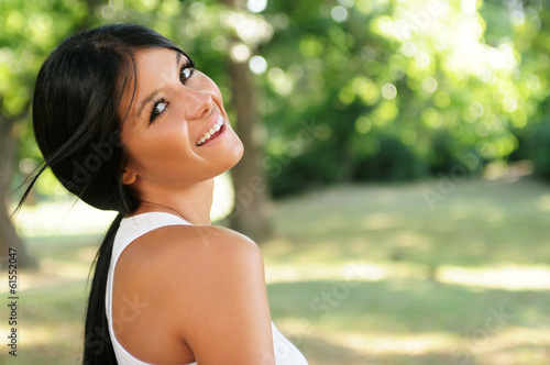 Portrait of beautiful happy young black haired woman in a park
