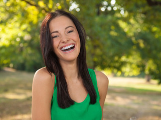 Friendly young woman with toothy smile outdoors portrait