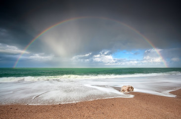 rainbow over Atlantic ocean waves on coast
