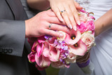 hands of bride and groom on beautiful wedding bouquet