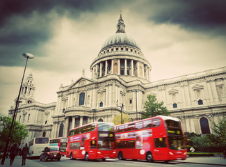 St Paul's Cathedral in London, the UK. Red buses, vintage style.