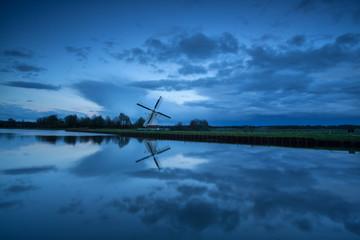 Dutch windmill by river in dusk