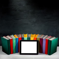 tablet with empty screen with colorful books on background with