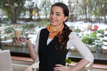 Waitress posing with cup of coffee in café or restaurant