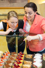 Two woman in cafe choosing cake