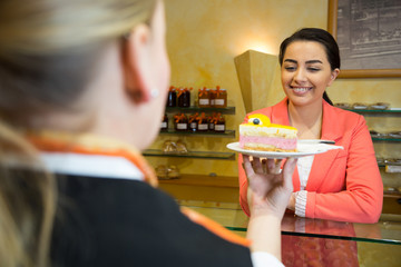 waitress serving cake to customer in café