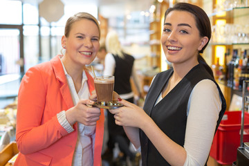 Waitress giving cup of coffee to customer in café