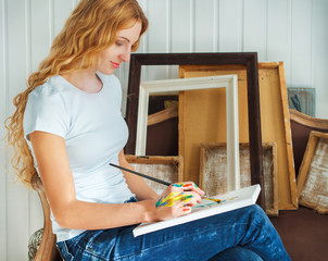 Portrait of female artist holding paintbrush