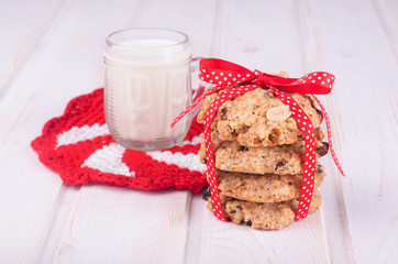 Homemade oatmeal cookies with nuts and milk with red ribbon