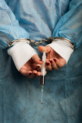 Criminal handcuffed medical person with bloody injector in hand