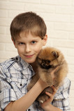 Adorable boy with Spitz puppy at home