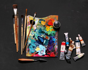 Professional brushes with a palette knife and tubes of paint