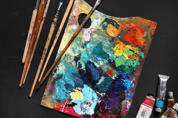 Professional brushes with palette and tubes of paint