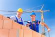 Bauarbeiter auf Baustelle mit Kran
