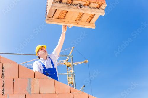 Maurer bekommt eine Palette Backsteine auf Baustelle
