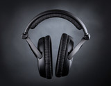 Modern headphones over black background