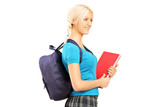 Schoolgirl holding textbooks and backpack walking