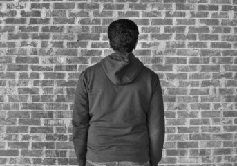 Young man with bricks wall as background,black and white