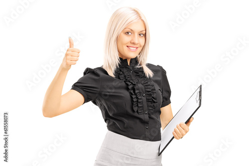 Young female worker holding clipboard and giving thumb up