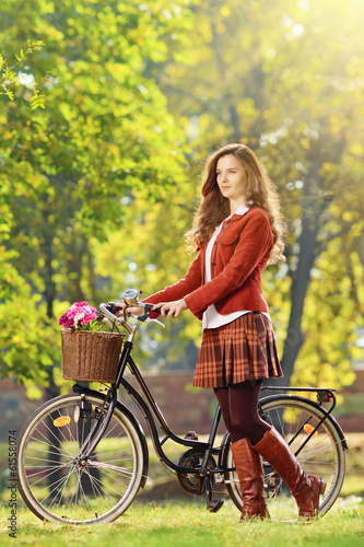 Young female with bicycle relaxing in a park