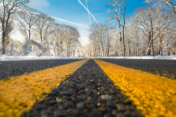 Yellow dividing line on road on winter day