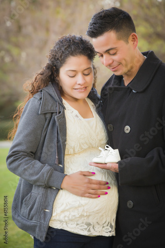 Hispanic Pregnant Couple Holding Baby Shoes Outside