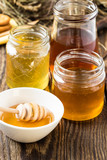 Honey in a glass jars on a wooden rustic background
