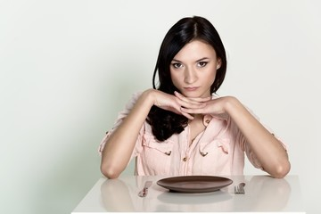 Beautiful brunette woman sitting with an empty plate