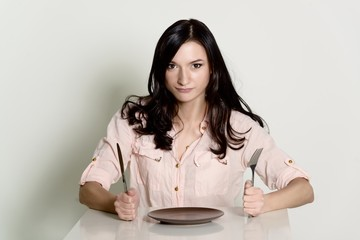 dissatisfied brunette woman waiting for a meal on an empty plate