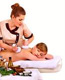 Woman getting herbal ball massage treatments .