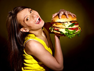 Woman holding hamburger.