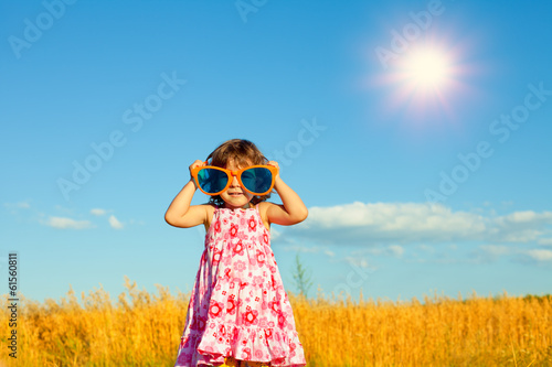 Happy little girl with big sunglasses in the wheat field - 61560811
