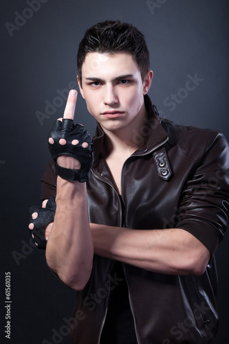 Angry handsome young man is showing a middle finger