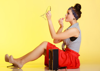 Cosmetic. Pin-up girl woman with bun applying makeup on yellow.