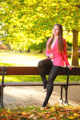 Fall. Full length girl woman sitting on bench in autumnal park