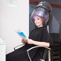 Woman client curlers in hair reads magazine hairdressing salon.
