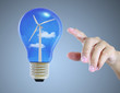 Hand pointing light bulb with wind turbine eco concept