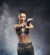 Beautiful redhead young woman with gun and military outfit, on s