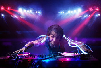 Disc jockey playing music with light beam effects on stage