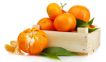 Ripe tasty tangerines with leaves in wooden box isolated