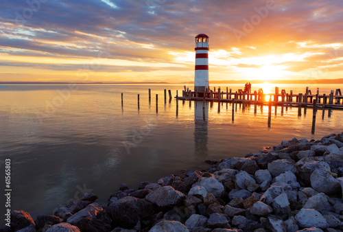 Ocean sunset with lighthouse - 61565803