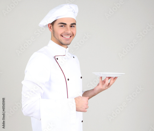 Professional chef in white uniform and hat, on gray background
