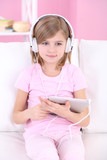 Little girl sitting on sofa and listening music in room