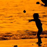 Silhouette  little  child on a beach at sunset
